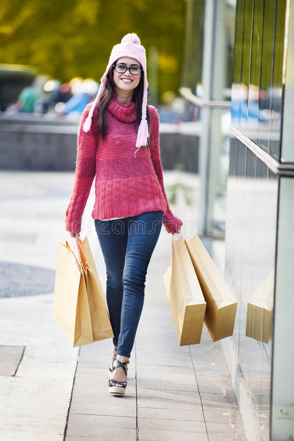 Cheerful shopper with brown shopping bags. Smiling female shopper carrying brown shopping bags at the shopping mall royalty free stock photo
