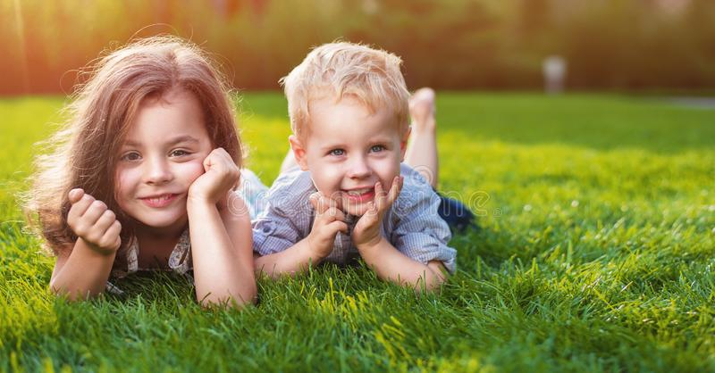 Cheerful siblings relaxing on a fresh lawn stock image