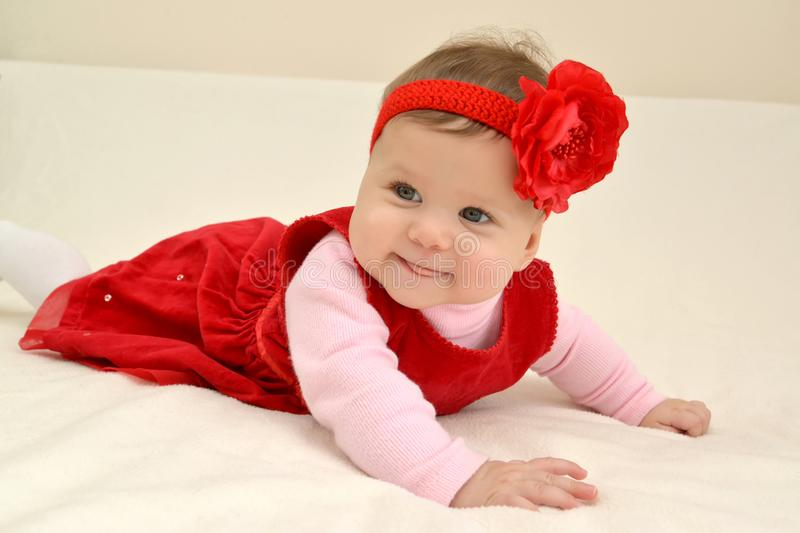 The cheerful six-months girl with a red flower on the head lies on a stomach royalty free stock photos