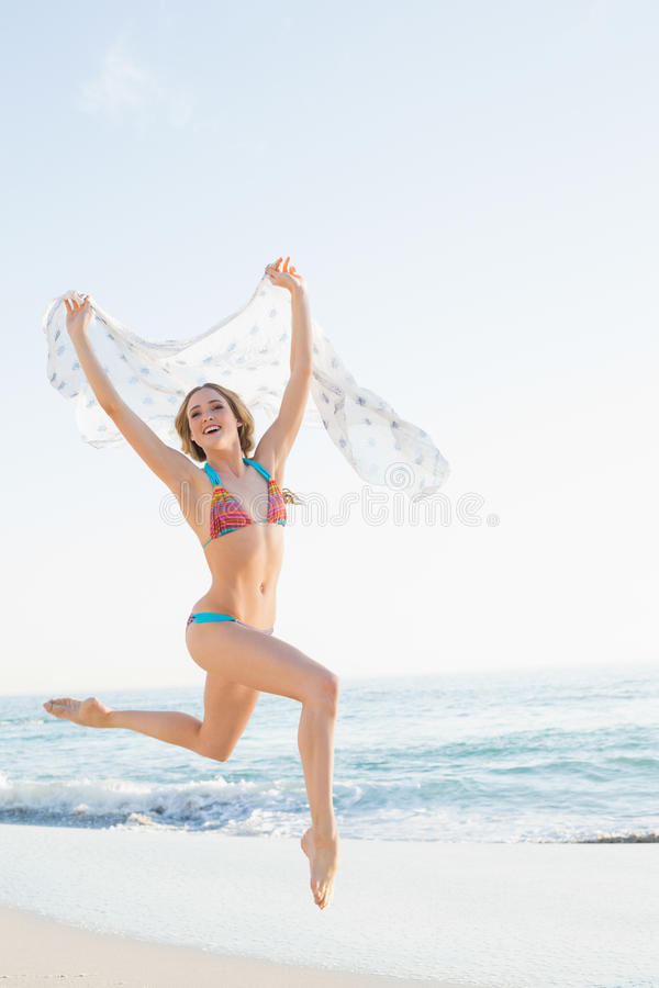 Cheerful slender woman jumping in the air holding shawl stock photography