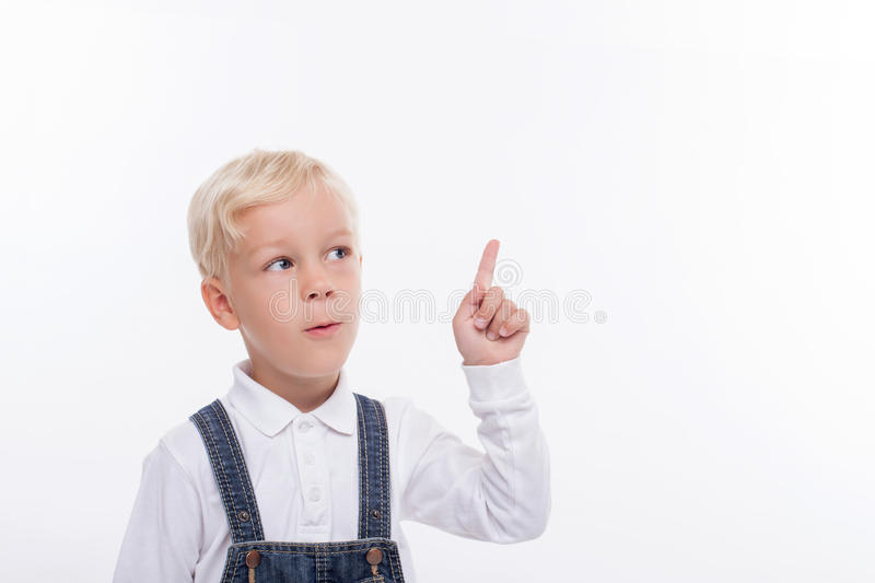 Cheerful small blond boy has a great idea. Pretty smart male child is standing and thinking about something. He is pointing his finger up pensively. Isolated and stock photography