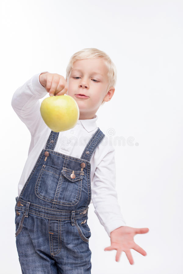 Cheerful small boy is eating healthy fruit. Cute male child is holding an apple and showing it to the camera. He is standing and gesturing emotionally. The royalty free stock photography