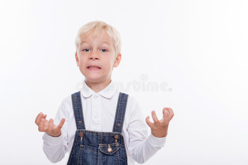 Cheerful small boy is expressing his negative. Angry male child is evincing his anger. He is looking at the camera with aggression. The schoolboy is strains his stock photography