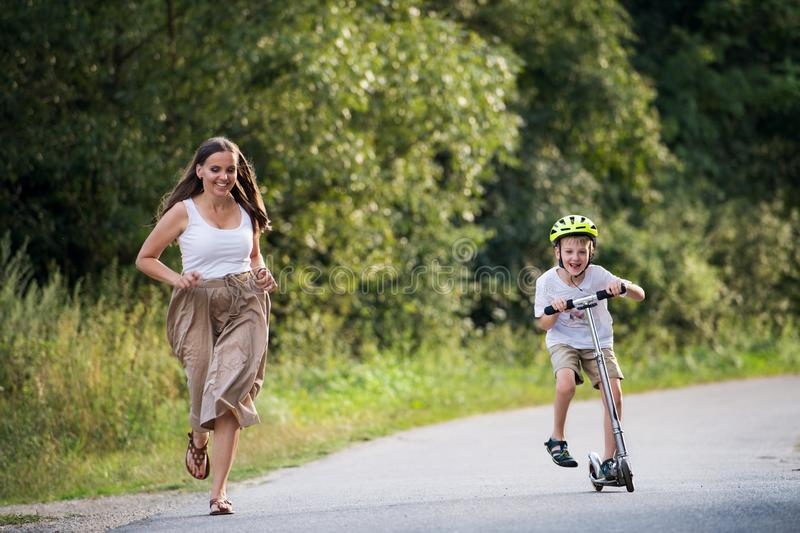 A small boy riding scooter and mother running on a road in park on a summer day. stock photos