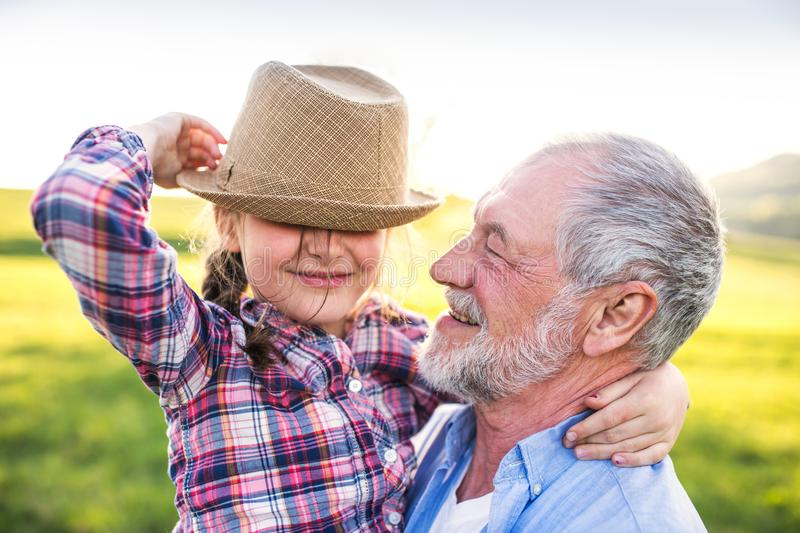 A small girl with grandfather outside in spring nature, having fun. royalty free stock photos