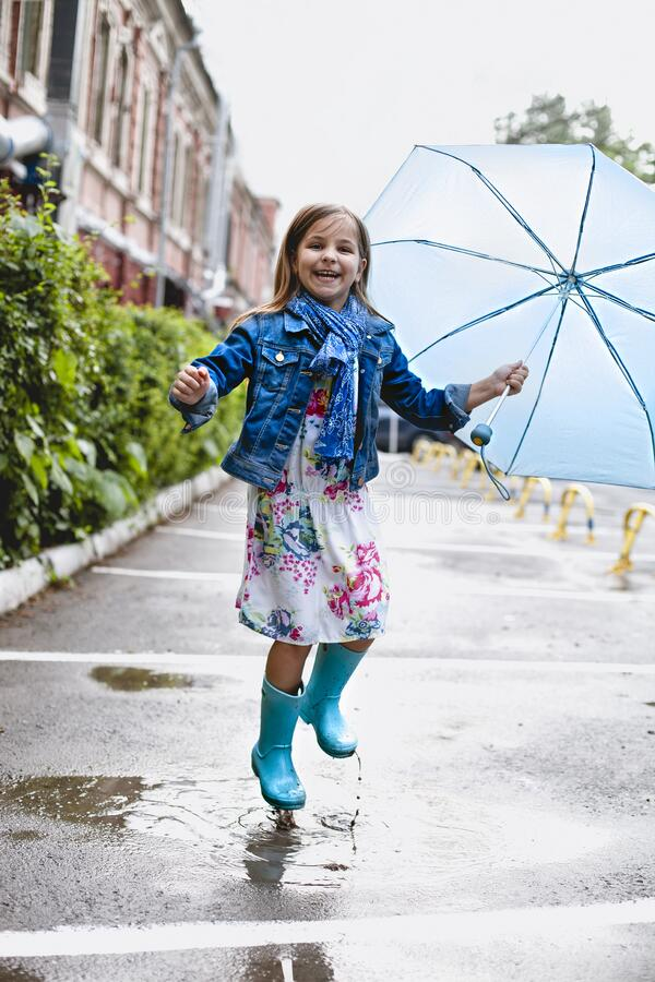Cheerful small girl having fun in puddle on street. Playful excited preschool child in casual clothes and rubber boots with blue umbrella laughing and jumping in royalty free stock image