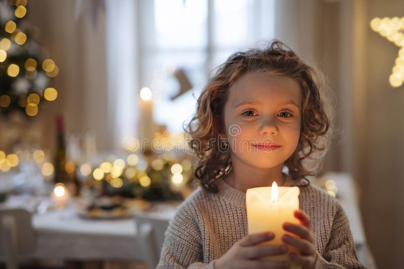 Cheerful small girl standing indoors at Christmas, holding candle. royalty free stock photography