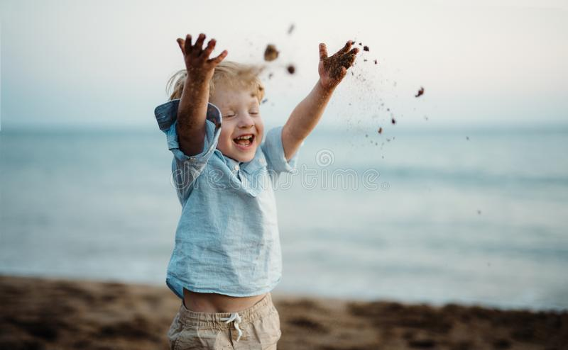 A small toddler boy standing on beach on summer holiday, throwing sand. royalty free stock photos