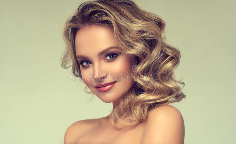 Pretty blond-haired model with curly, loose hairstyle and attractive makeup. Cheerful and smiley face of lovely,young woman. Pretty blond-haired model with stock photos