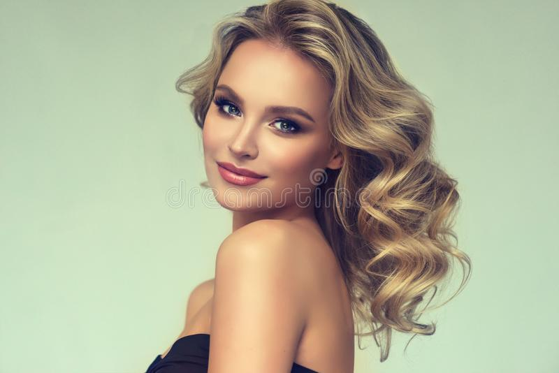 Pretty blond-haired model with curly, loose hairstyle and attractive makeup. Cheerful and smiley face of lovely,young woman. Pretty blond-haired model with royalty free stock photos