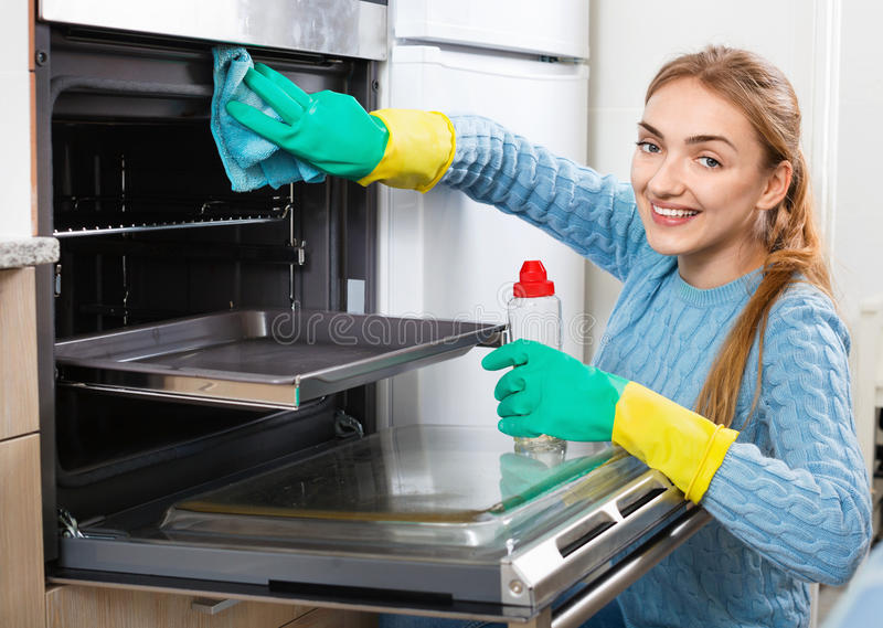 Cheerful smiling adult girl removing snuff in oven royalty free stock photo