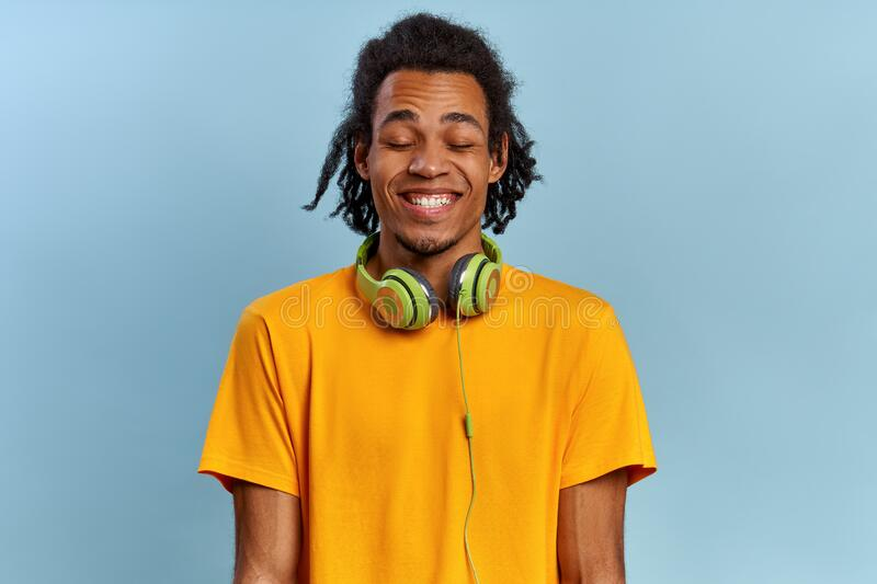 Cheerful smiling african-american guy with closed eyes from pleasure stock photography