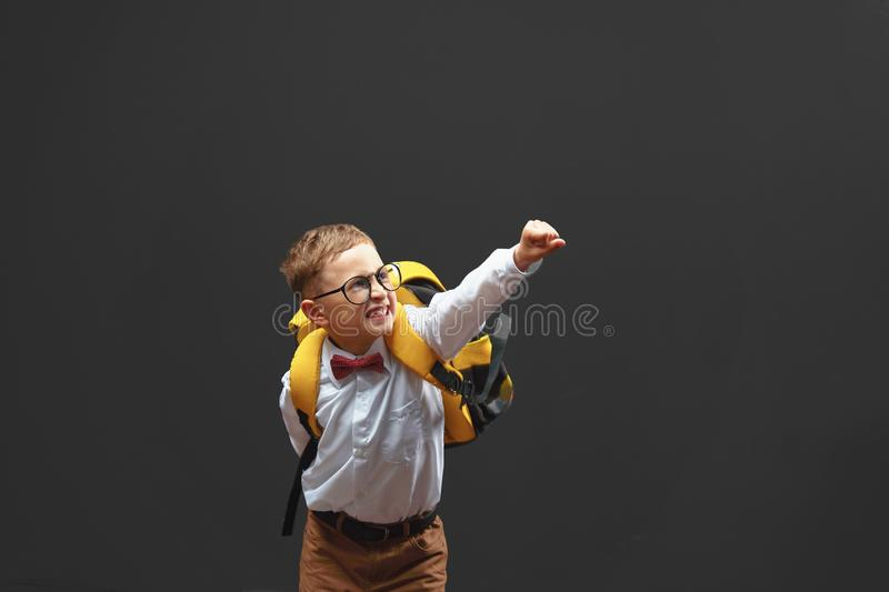 Cheerful smiling baby boy on a dark background raised his hands up demonstrating the desire to win. The concept of school and stock image
