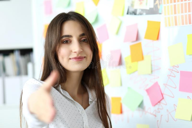 Cheerful smiling beautiful female clerk welcoming business partner. By shaking hand as sign of future achievements and prospects headshot stock image