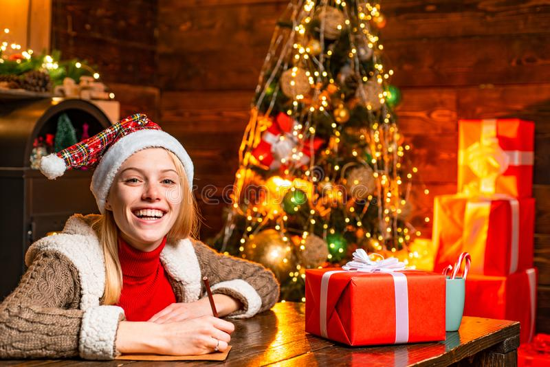 Cheerful smiling blonde woman writing a letter to Santa with her wish list of presents. Christmas presents gifts concept stock photos