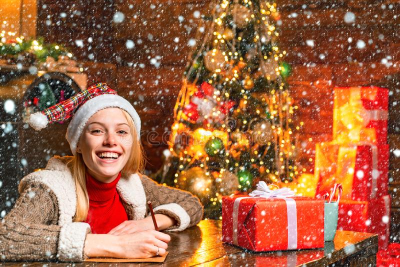 Cheerful smiling blonde woman writing a letter to Santa with her wish list of presents. Christmas presents gifts concept royalty free stock photos