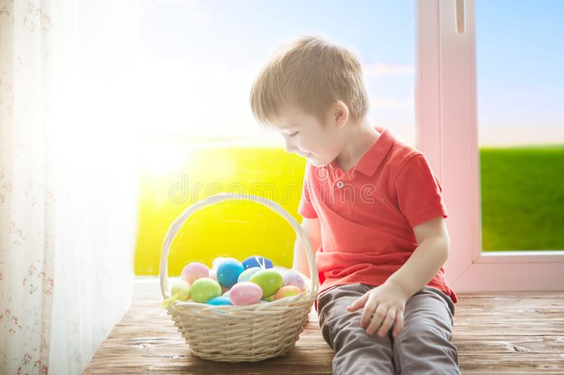 Cheerful smiling boy holding basket full of colorful easter eggs and sitting on the windowsill against the background of spring stock images