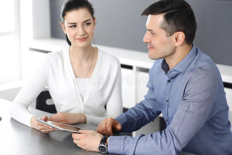 Cheerful smiling businessman and woman working with tablet computer in modern office. Headshot at meeting or workplace stock photography