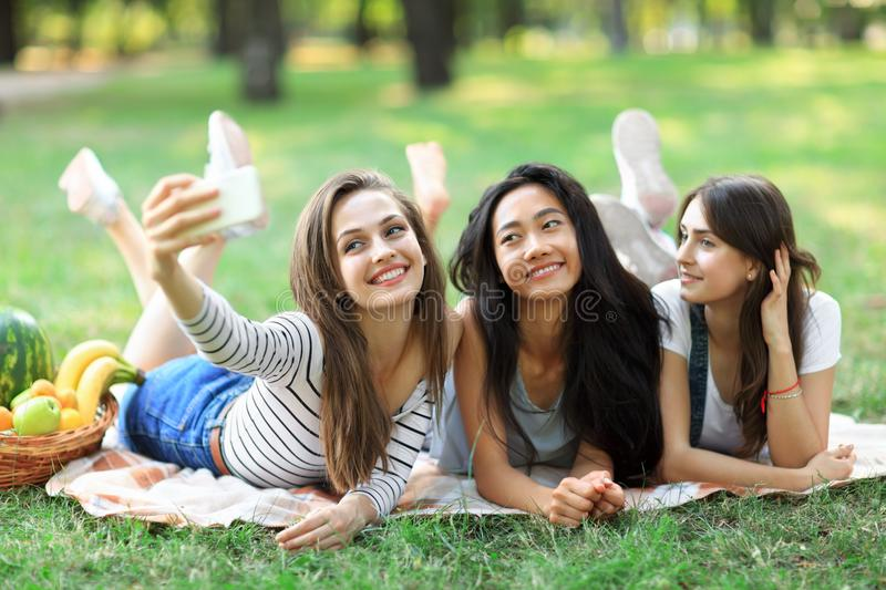 Cheerful smiling girls taking selfie lying on blanket on grass stock photography