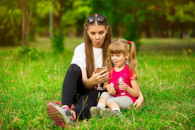 Cheerful smiling happy mother and her little daughter are sitting on green grass in summer park royalty free stock image