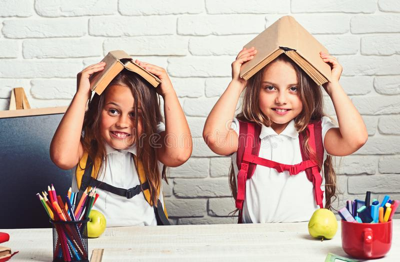 Cheerful smiling little girls with books on head. Looking at camera. School concept. Back to School. Cheerful smiling little girls with books on head. Looking royalty free stock photo