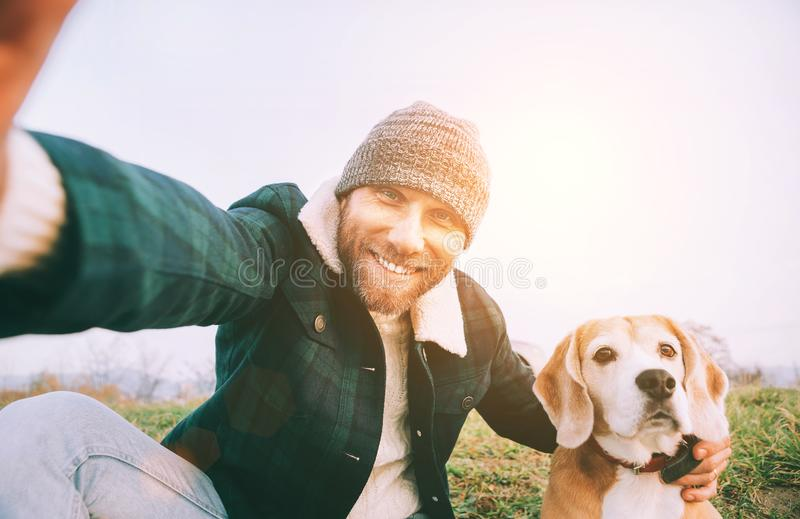Cheerful smiling Man takes selfie photo with his best friend beagle dog during walking. Human and pets concept image stock photography