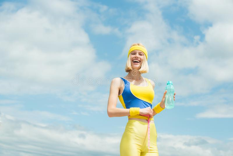 Cheerful smiling sporty girl with bottle of water at blue cloudy sky background. Beautiful blonde woman girl doing sport stock photo