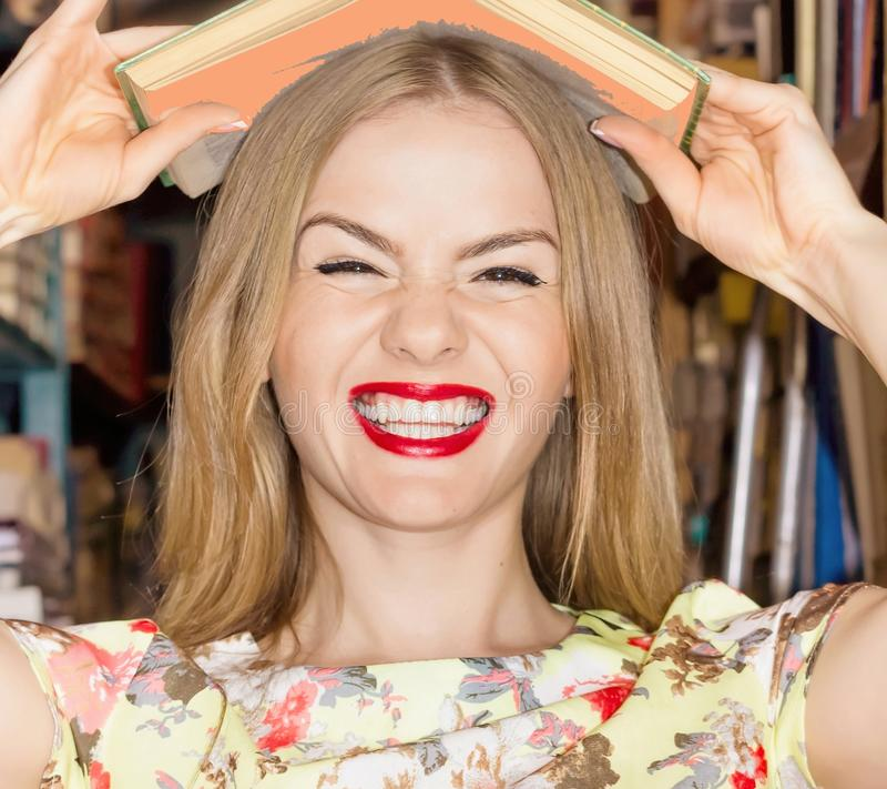 Cheerful smiling student holding big heavy books on her head. Lo royalty free stock photo