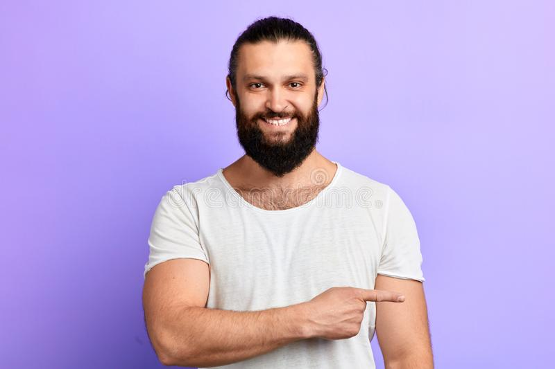 Cheerful smiling unshaven man pointing at copy sace royalty free stock photos