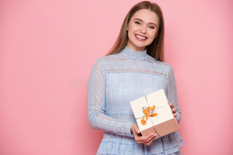 Cheerful smiling young adult woman holding present box on pink background. Cheerful smiling young adult woman holding present box on pink background royalty free stock photos