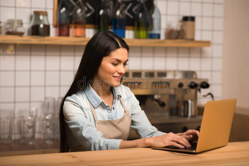 Cafe owner using laptop. Cheerful smiling young cafe owner using laptop stock images