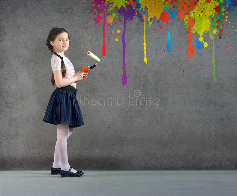 Cheerful smiling young little girl the child draws on the background wall colored paints making a creative repairs. stock image