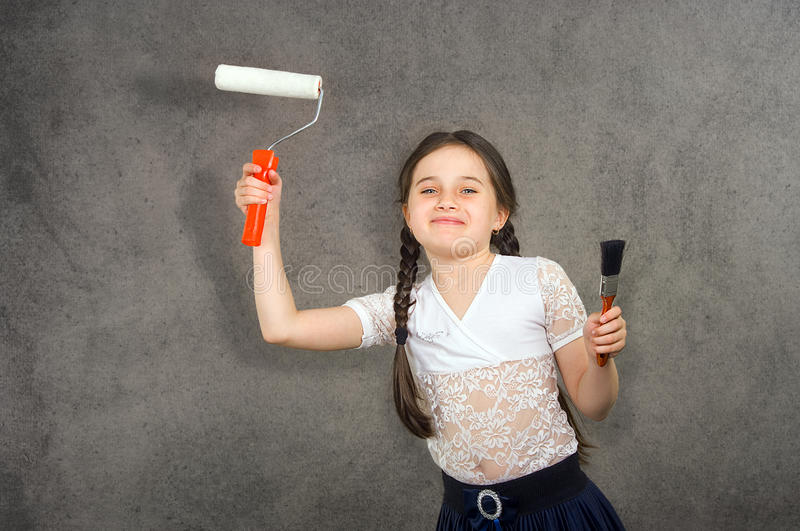 Cheerful smiling young little girl the child draws on the background wall colors making a creative repairs. stock photography