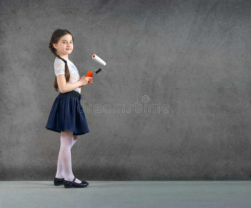 Cheerful smiling young little girl the child draws on the background wall colors making a creative repairs. royalty free stock photography