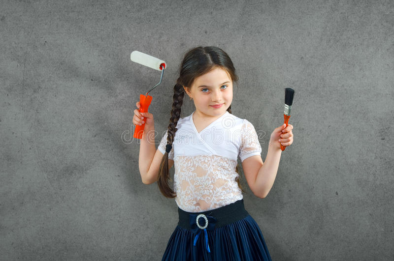 Cheerful smiling young little girl the child draws on the background wall colors making a creative repairs. stock images