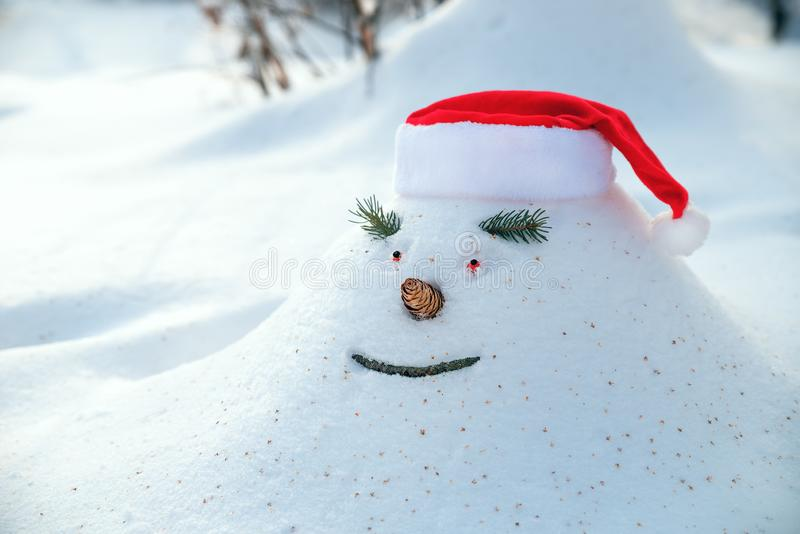Cheerful snowdrift, snowman in anticipation of waiting for Christmas holidays in a snowy forest. royalty free stock images