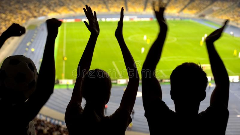 Cheerful soccer fans clapping at crowded stadium, supporting national sport team royalty free stock photos