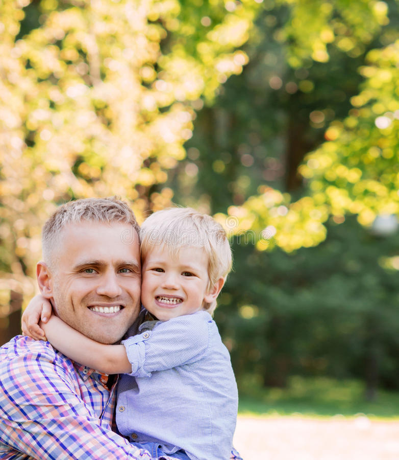 Cheerful son giving a hug to his father in the park stock photo