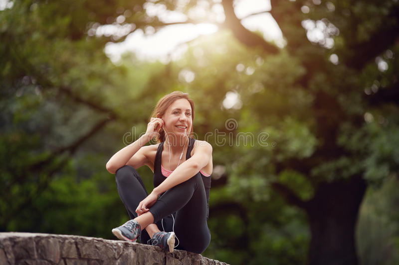 Cheerful sportswoman with headphones in park royalty free stock photo