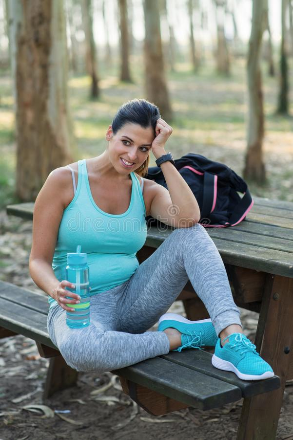Sporty pregnant woman resting and drinking water royalty free stock photography