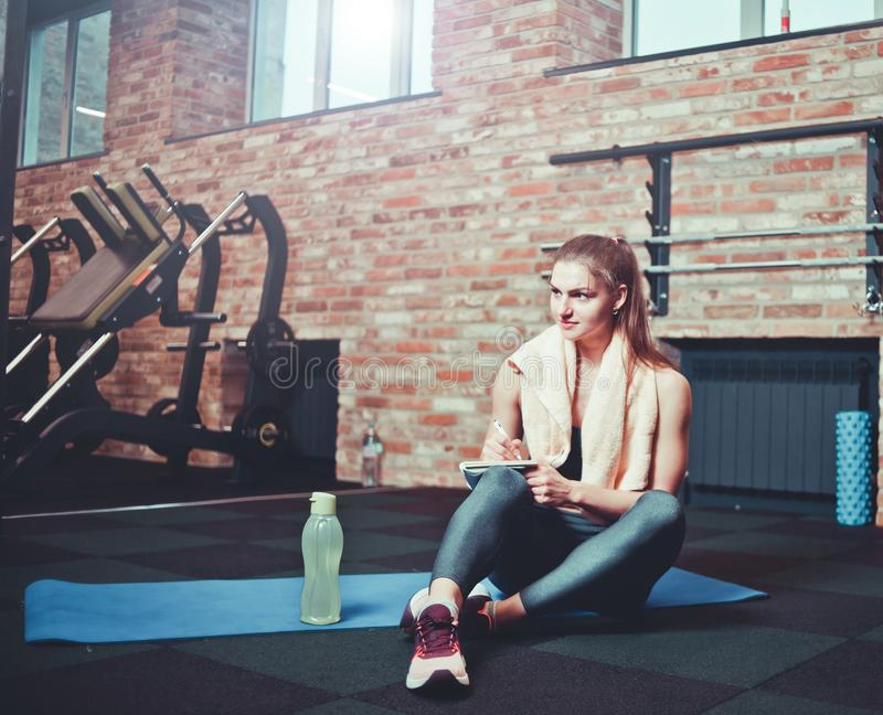 Cheerful sporty woman. Cheerful sporty women sits on a training mat and writes down future training plans for achieving great results in gym royalty free stock image