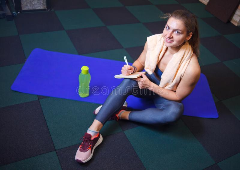 Cheerful sporty woman. Sits and resting on a training mat and writes down future training plans for achieving great results in gym royalty free stock photo
