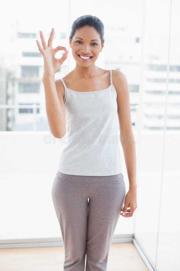 Cheerful sporty young woman making okay gesture stock image