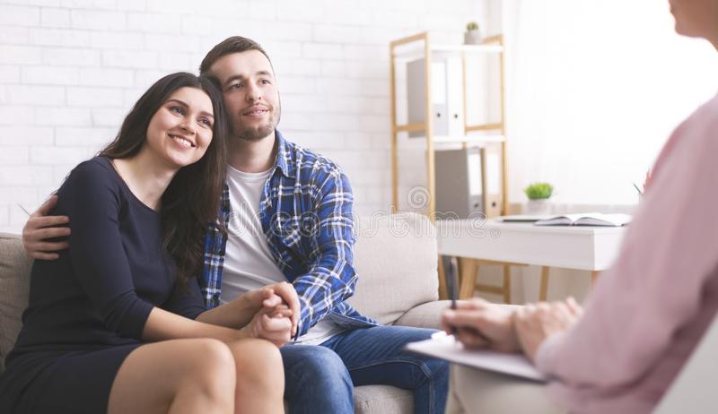 Cheerful spouses bonding at consultation with psychologist. Cheerful millennial spouses bonding at consultation with personal psychologist, free space royalty free stock images