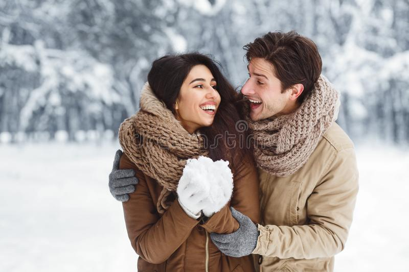 Cheerful Spouses Holding Snow And Hugging Standing In Winter Forest royalty free stock photo