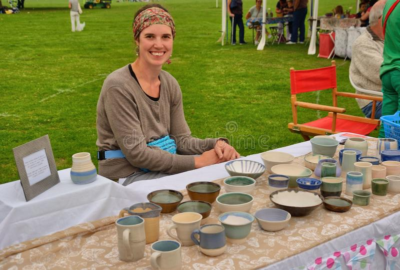 Cheerful stallholder. Happy potter displaying her pottery at a market stall