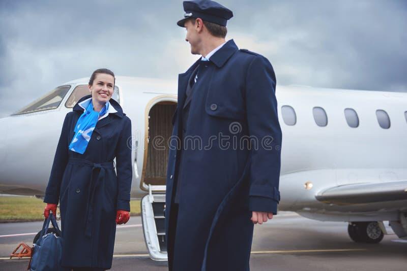 Cheerful stewardess speaking with aviator stock photos