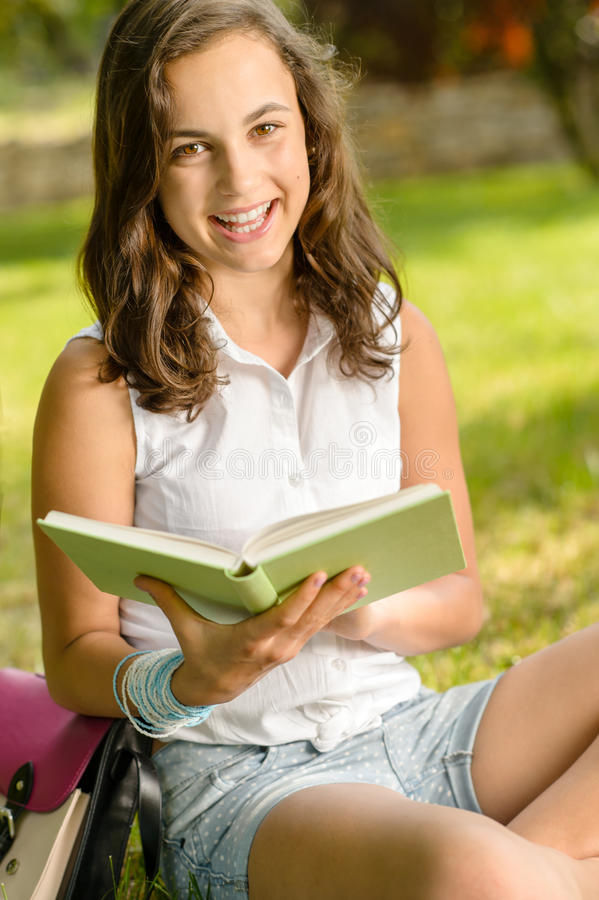 Cheerful student girl sitting grass read book royalty free stock photography