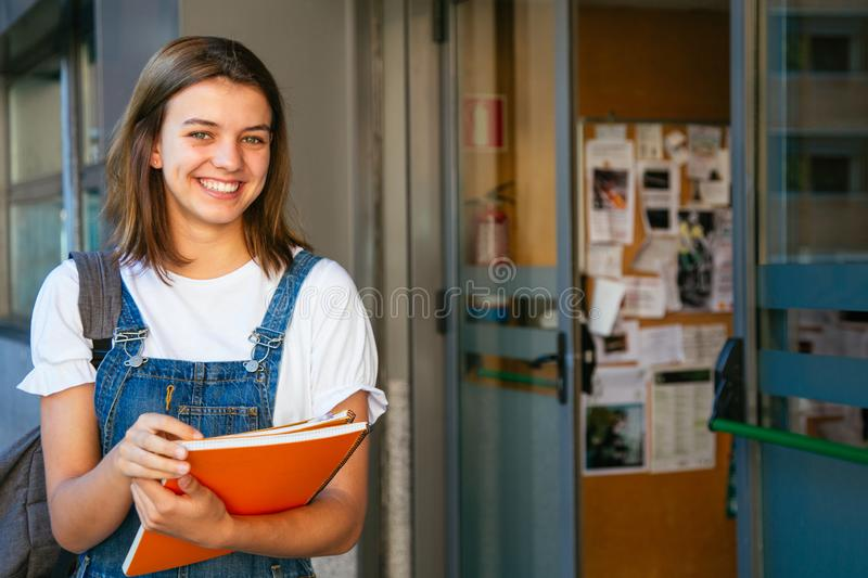 Cheerful student girl about to enter class stock photography