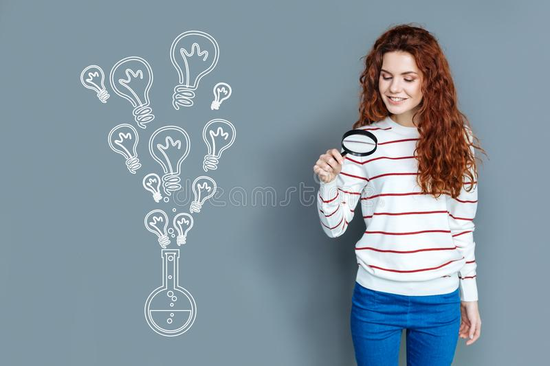 Cheerful student holding a magnifying glass and smiling. Interesting experiment. Positive curious student standing with a magnifying glass while making an stock image